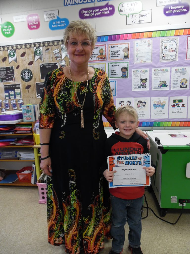 student holds a certificate while standing next to a literacy specialist