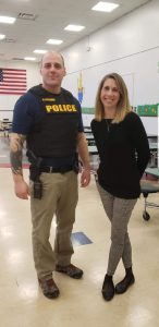 officer in uniform with a school principal in a school cafeteria