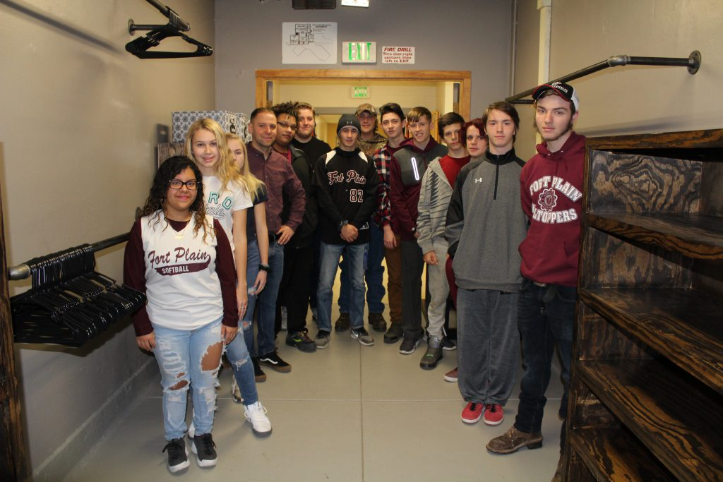Group of students and their teacher stand inside a large walk-in closet space