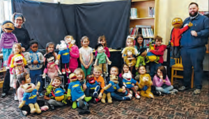 group of elementary students pose in a school library holding puppets