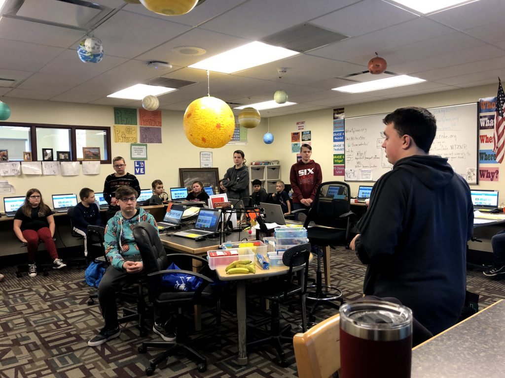 high school student leads a lesson for fourth graders in a school computer lab