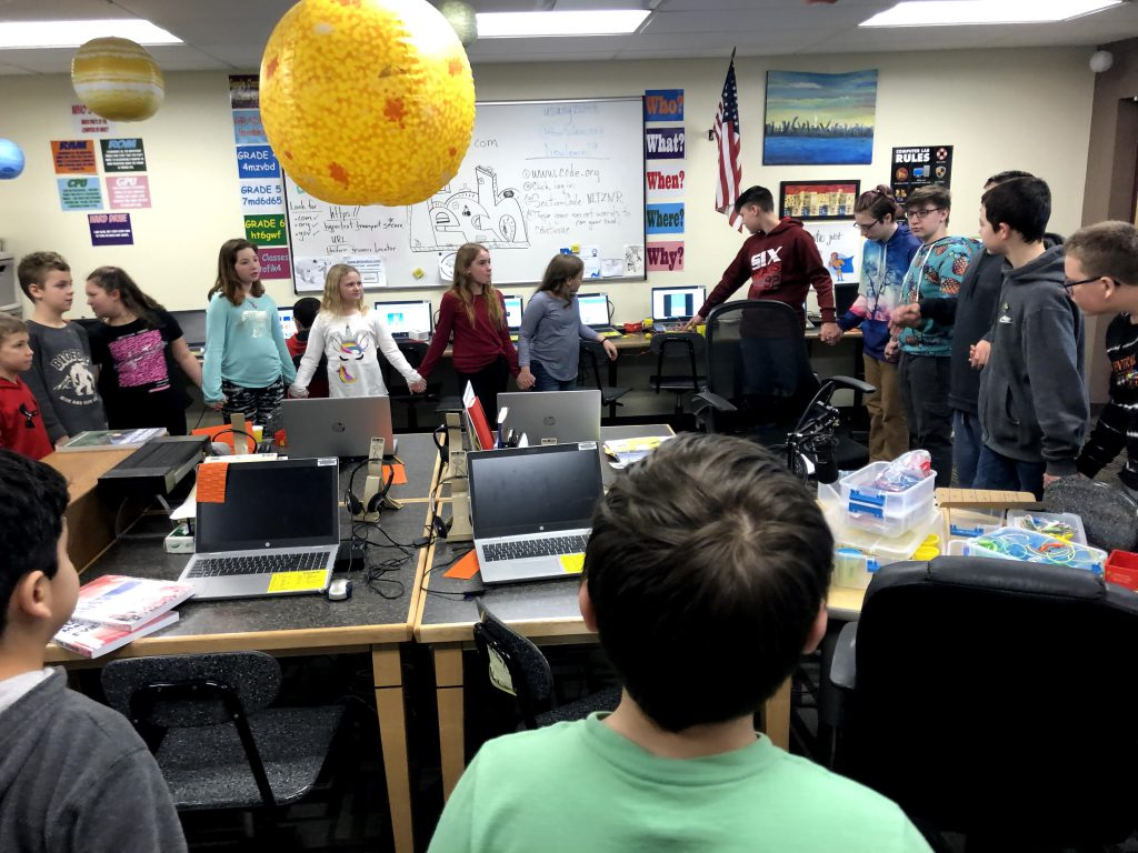 Students hold hands in a circle in a computer lab
