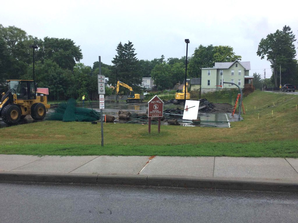 construction equipment removes surface of tennis court at high school