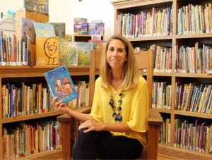school principal holds picture book seated in a chair in a school library