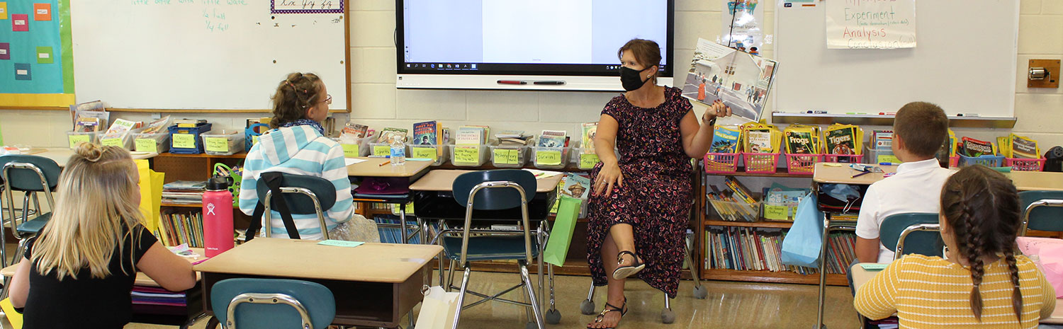 teacher reading book to students in classroom