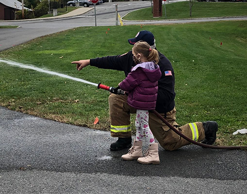 Student learning how to use a fire hose