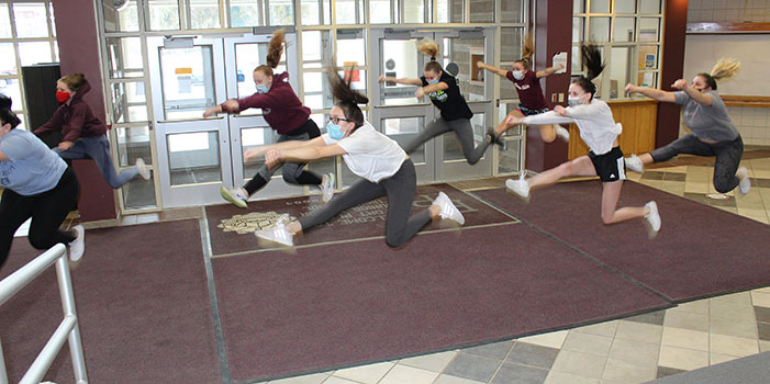 cheerleaders leaping during practice in HS lobby