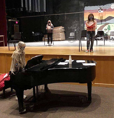 students reading scripts on stage while teacher plays the piano
