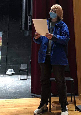 student reading script, standing on stage