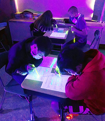 students working at desks in blacklighted classroom