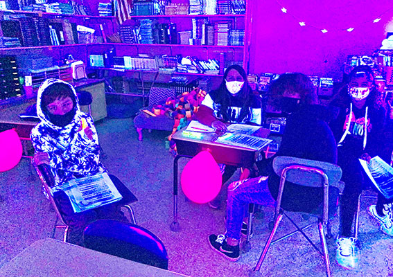teacher and students in blacklighted classroom