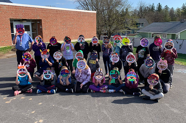 group of students and teacher holding their Kachina Masks in front of their faces