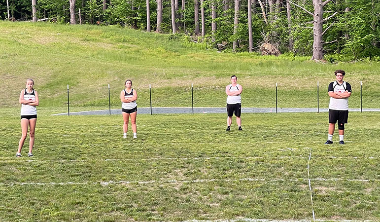 Four students standing on discus field