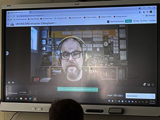 Alan Gratz on video screen talking to students in classroom