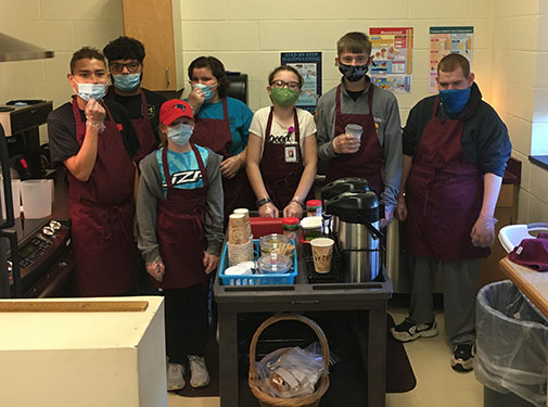 students standing in their classroom's kitchen area behind the coffee cart