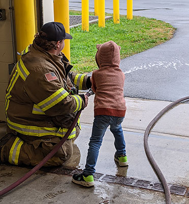 Firefighter and student holding a hose