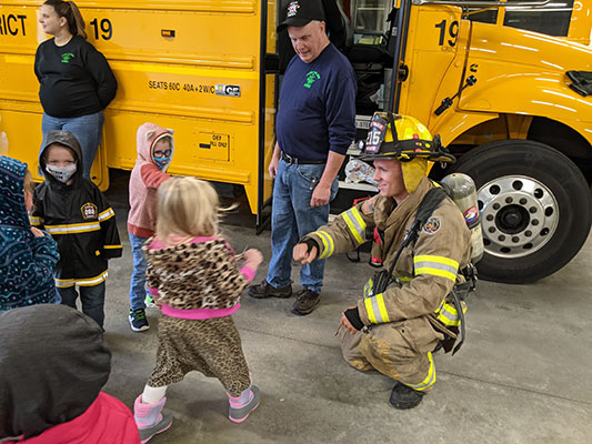 Firefighter kneeling to greet a Pre-K student