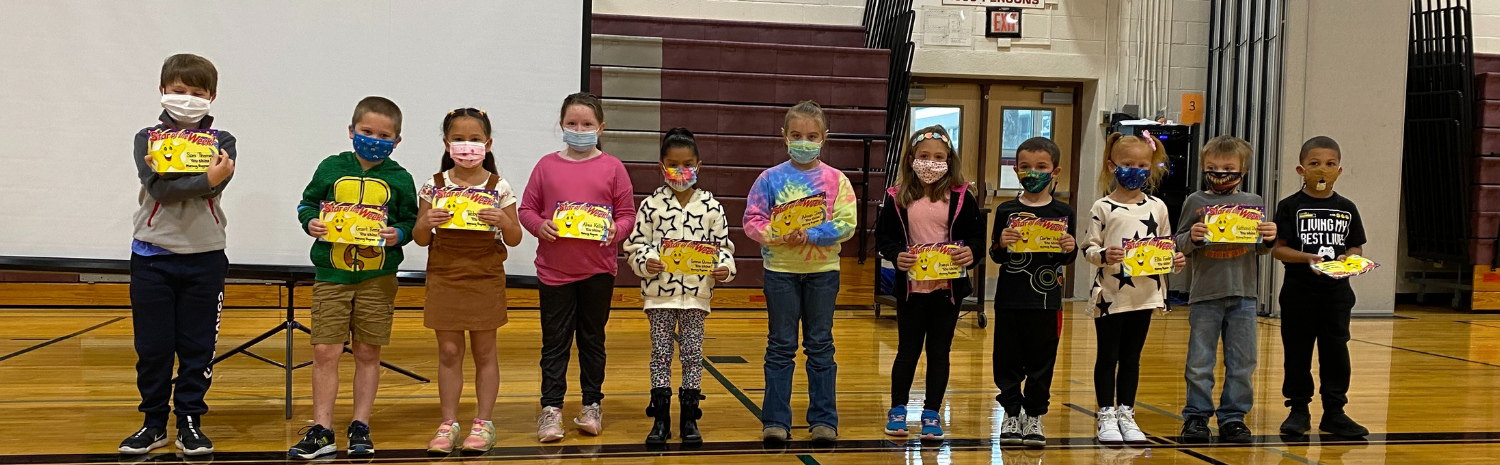 elementary students holding certificates, standing in a row